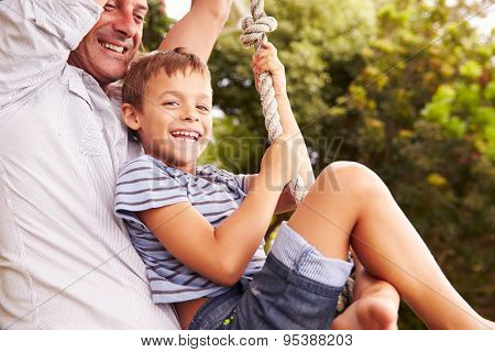 Father swinging with son at a playground
