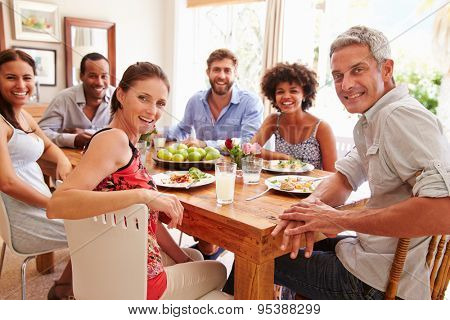 Friends sitting at a dining table, looking at camera
