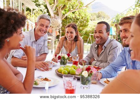 Friends dining together at a table in a garden