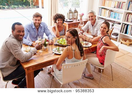 Friends sitting at a dining table looking at the camera