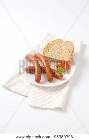 hot frankfurter sausages and slice of bread on white plate