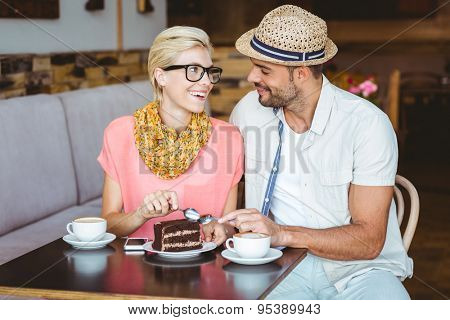 Cute couple on a date eating a piece of chocolate cake at the cafe