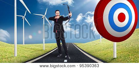 Focused businessman shooting a bow and arrow against road leading out to the horizon with wind turbines either side