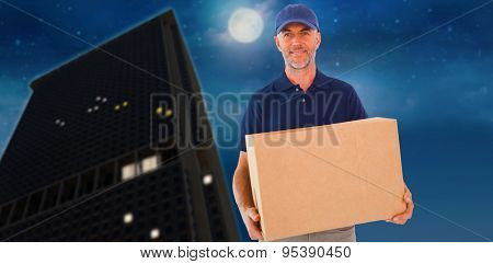 Happy delivery man holding cardboard box against city at night