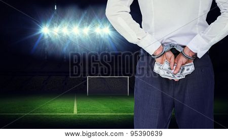 Businessman in handcuffs holding bribe against football pitch under spotlights
