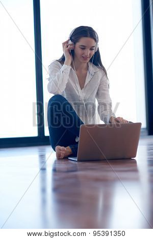 beautiful young woman relax and work on laptop computer modern  home office while listening music on white headphones