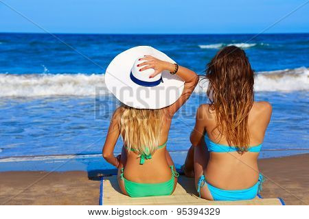 Beach girls rear back view sitting in the beach looking horizon in summer