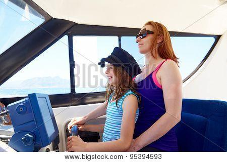 Kid girl pretending be a captain sailor cap with her mother in boat indoor