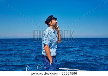 Captain cap sailor man talking mobile phone in boat sailing in the ocean sea