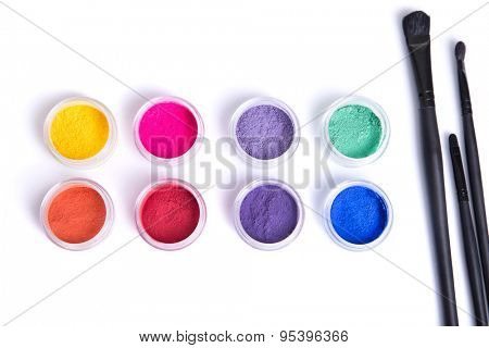 Top view of matte mineral eye shadows and makeup brushes, isolated on white background