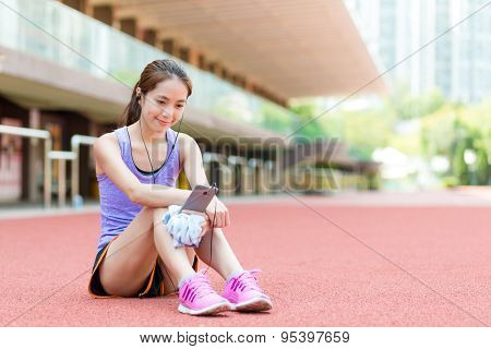 Woman sitting on stadium and listening to music after doing exercise