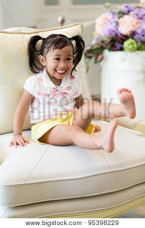 Thrilled little girl sitting on couch