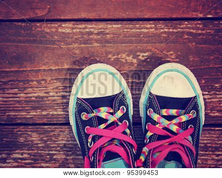 a wide angle photo of a pair of generic looking shoes like converse sneakers with pink shoe laces on a vintage wooden background toned with a retro vintage instagram filter app