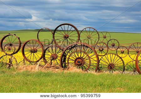 Rusty wheels fence with scenic background
