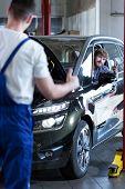 pic of car repair shop  - Fixing a car in auto repair shop - JPG