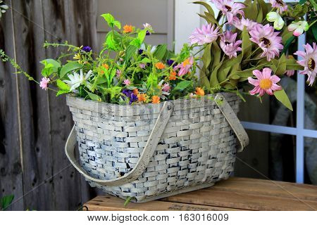Pretty basket with handles, filled with variety of wildflowers, set  on outdoor table.