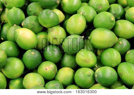 Background of fresh picked limes stacked together at local farmers  market.