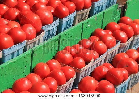 Blue pint containers filled with fresh picked tomatoes at local market.
