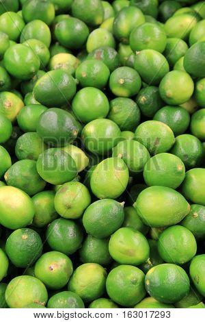 Vertical image of fresh limes stacked together on table at local market.
