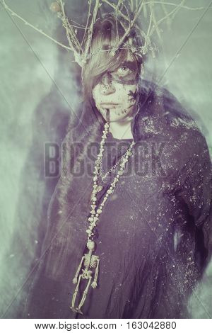Serious shaman on a winter field looking at camera