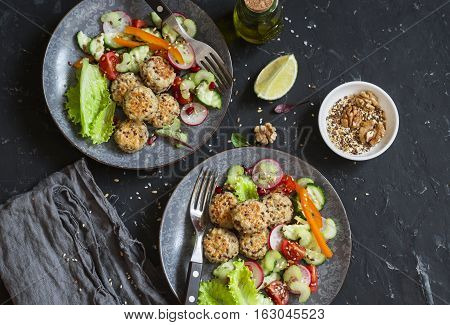 Vegetarian lunch - quinoa meatballs and vegetable salad on a dark table top view