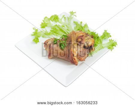 Baked ham hock with lettuce and parsley on a square white dish on a light background