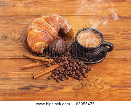 Freshly brewed coffee latte in a black ceramic cup roasted coffee beans cinnamon sticks chocolate truffle and croissant on a glass saucer on an old wooden surface