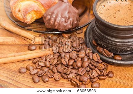 Pile of roasted coffee beans with cinnamon sticks and fragment of black ceramic cup with freshly brewed coffee on the background of chocolate truffle and croissant on a wooden surface