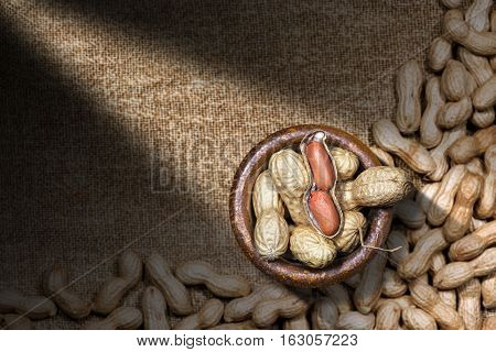 Group of peanuts in shell with one shelled (open). In a wooden bowl on a brown canvas with dark shadows