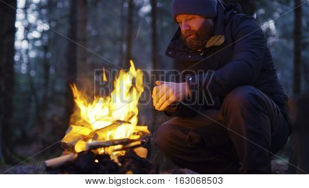 One pensive man with beard warms himself by the campfire outdoors in the woods a cold winter evening. Bonfire in the forest filmed with dolly.