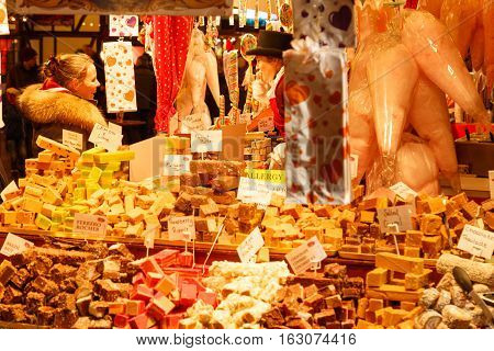 NOTTINGHAM ENGLAND - DECEMBER 22: Woman buying at sweet/candy stall at Nottingham Christmas market at night. In Nottingham England. On 22nd December 2016.