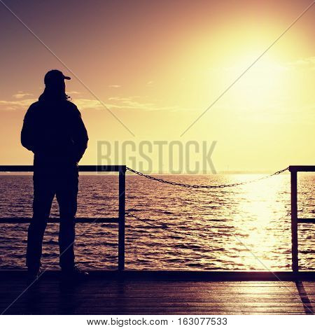 Tall Man Stand On Mole Wooden Board And Looking Over Ocean To Sun. Empty Wharf,