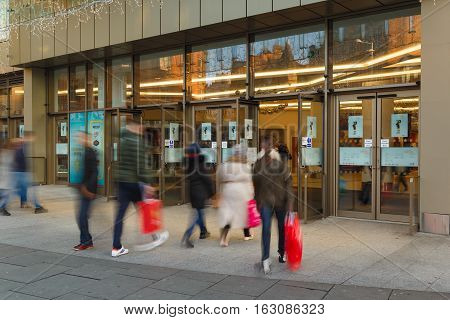 NOTTINGHAM ENGLAND - DECEMBER 26: People enter INTU Victoria Centre shopping mall with bags on Boxing Day sales. In Nottingham England. On 26th December 2016.