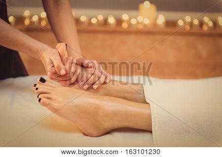 Close up of masseuse hands massaging female foot at beauty salon