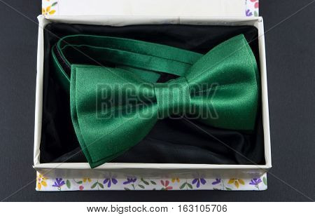 Green Bow Tie In Present Box On Black Background