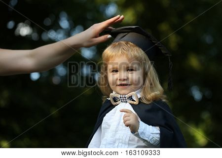 Little boy child in black academic gown and squared school hat and bow tie with blonde hair on smiling face standing outdoor on green natural background with female hand