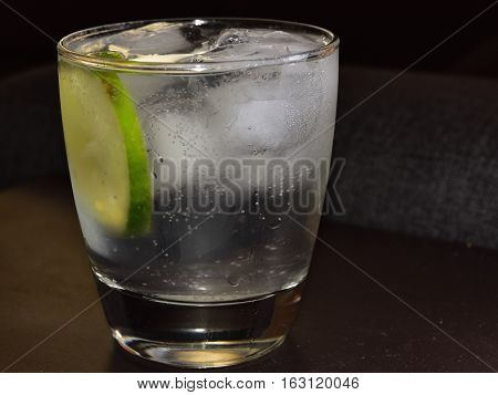 A nice glass of vodka and tonic with a lime twist.