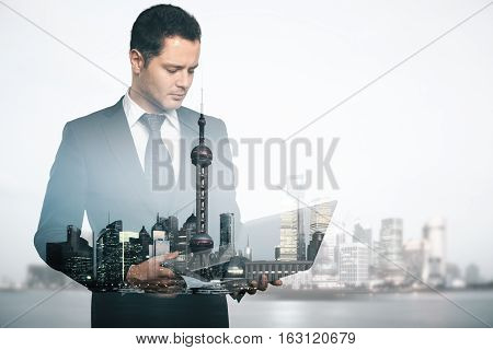 Abstract image of caucasian gentleman using laptop on city background. Double exposure. Communication concept