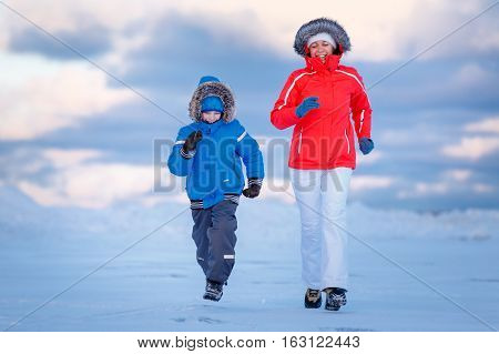 Cute little boy and his mother on icy beach, winter family holiday