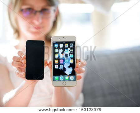 PARIS FRANCE - SEp 29 2016: New Apple iPhone 7 being presented and compared by woman with iPhone SE phone in terms of size and specs. New Apple iPhone tends to become one of the most popular smart phones in the world in 2016