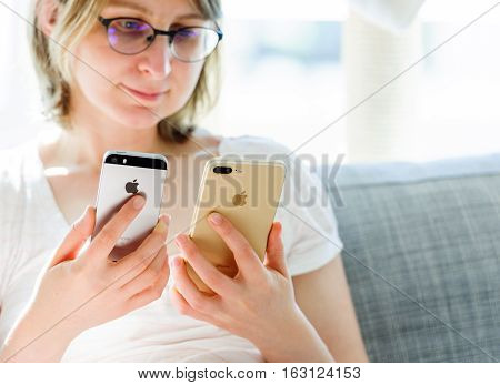PARIS FRANCE - SEP 29 2016: New Apple iPhone 7 being compared by woman with iPhone SE phone in terms of size and specs. New Apple iPhone tends to become one of the most popular smart phones in the world in 2016
