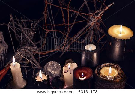 Black magic candles against evil background. Halloween concept, mystic ritual or spell with occult and esoteric symbols, divination rite. Vintage objects in the darkness