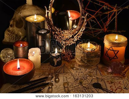 Mystic still life with magic mirror, demon paper and candles. Halloween concept. Esoteric objects on table. There is no foreign text in the image, all symbols are imaginary and fantasy ones