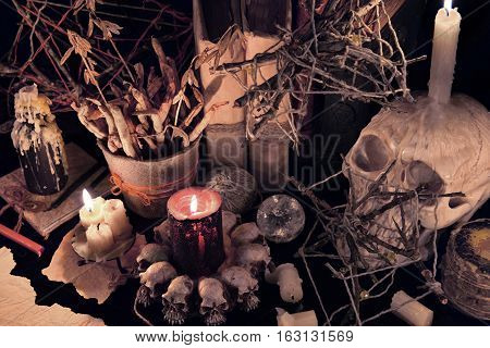 Mystic still life with evil candles and skull. Halloween concept, black magic ritual or spell with occult and esoteric symbols, divination rite. Vintage objects on witch table