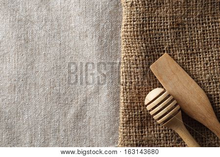 Wooden dipper kitchenware on sack and white wood board background