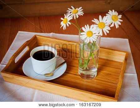 Coffee and chamomiles on wooden table. Selective focus