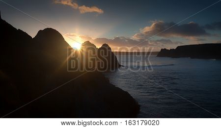 Sunset at Three Cliffs Bay Sun setting on the famous rockface at Three Cliffs Bay on the Gower peninsula in Swansea, South Wales
