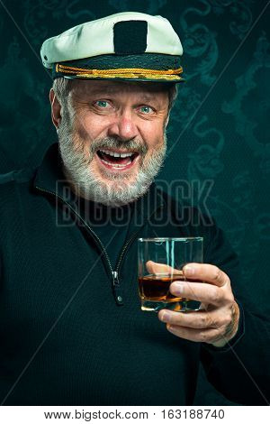 Portrait of old sailor man as captain in black sweater and hat drinking cognac on black studio background