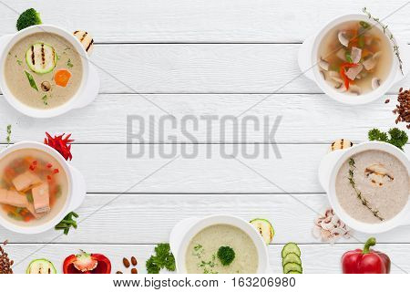 Set of different appetizing soups frame on wood flat lay. Top view on white wooden table with buffet serving of restaurant hot dishes. Worldwide cuisine, healthy food, lunch, menu concept