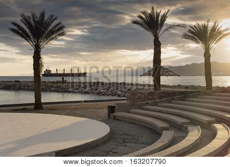 Sunset at the Red Sea; view from stone amphitheater on central public beach of Eilat - famous resort and recreational city in Israel